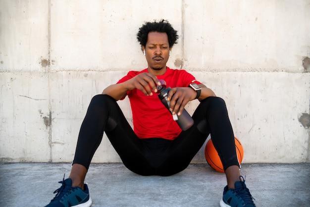 Ritratto di atleta afro uomo acqua potabile dopo il lavoro fuori all'aperto. sport e stile di vita sano.