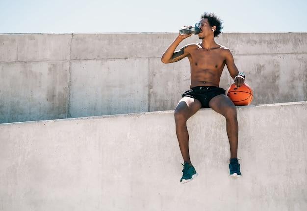 Ritratto di atleta afro uomo acqua potabile e tenendo la palla da basket all'aperto