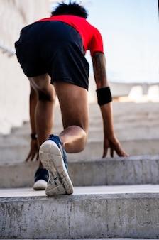 Ritratto di uomo atleta afro in posizione di partenza preparandosi a correre all'aperto
