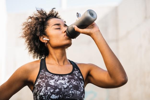 Ritratto di donna afro atleta acqua potabile dopo il lavoro fuori all'aperto