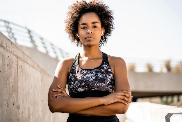 Ritratto di donna atleta afro in piedi all'aperto sulla strada