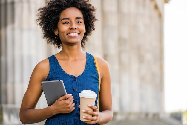 Ritratto di donna d'affari afro che tiene una tavoletta digitale e una tazza di caffè, mentre in piedi all'aperto sulla strada