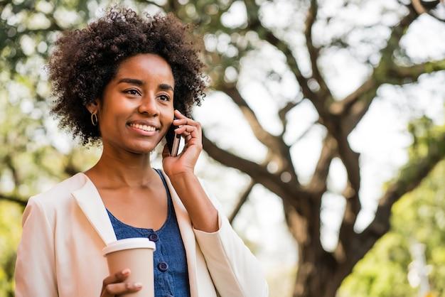 Ritratto di donna d'affari afro parlando al telefono e tenendo una tazza di caffè mentre si sta in piedi all'aperto al parco