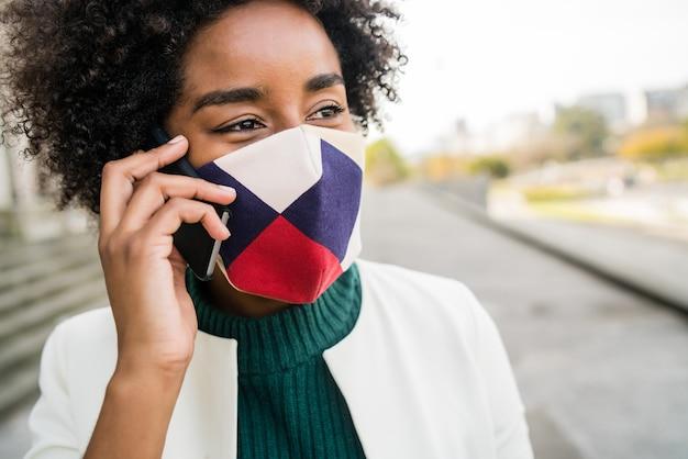 Ritratto di donna d'affari afro indossando maschera protettiva e parlando al telefono mentre si trovava all'aperto in strada. business e concetto urbano.