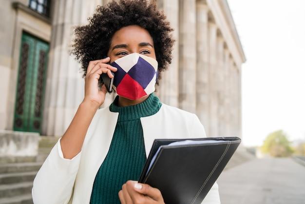 Ritratto di donna d'affari afro indossando maschera protettiva e parlando al telefono