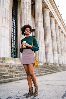 Ritratto di afro imprenditrice tenendo una tazza di caffè mentre si cammina all'aperto in strada