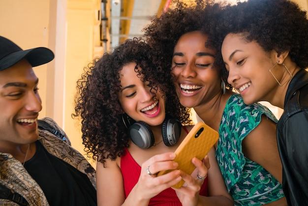 Ritratto di amici afro che si divertono in città e trascorrono del tempo insieme mentre usano il loro telefono cellulare. amicizia e concetto di stile di vita.