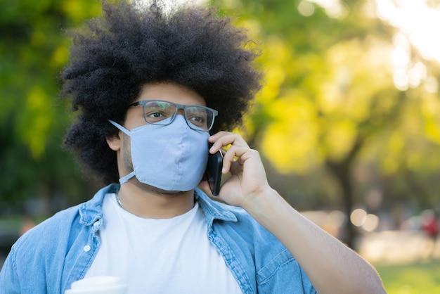 Ritratto di afro latino uomo che indossa la maschera per il viso e parlando al telefono