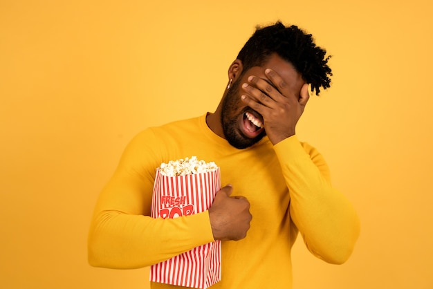 Ritratto di un uomo afro che mangia popcorn mentre guarda film su uno sfondo isolato.