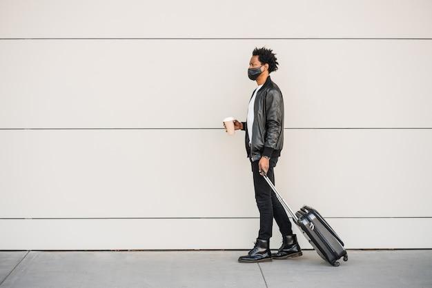Ritratto di turista afro uomo che porta la valigia e che tiene una tazza di caffè mentre si cammina all'aperto sulla strada. concetto di turismo.
