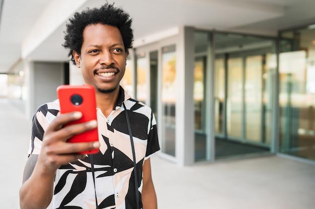 Ritratto di turista afro uomo utilizzando il suo telefono cellulare mentre si cammina all'aperto sulla strada.
