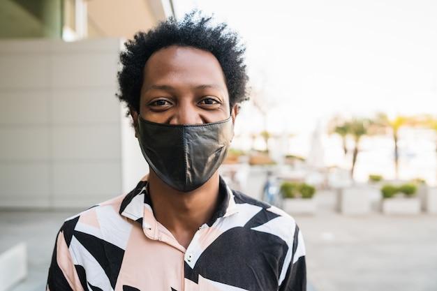Ritratto di turista afro uomo che indossa la maschera protettiva mentre in piedi all'aperto sulla strada. concetto urbano e lifestyle.