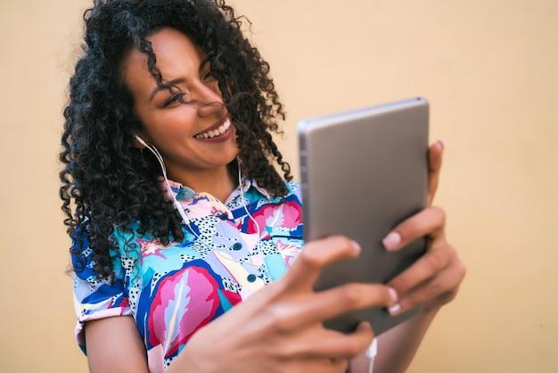 Ritratto di donna afro che cattura selfie con la sua tavoletta digitale contro il muro giallo. concetto di tecnologia.