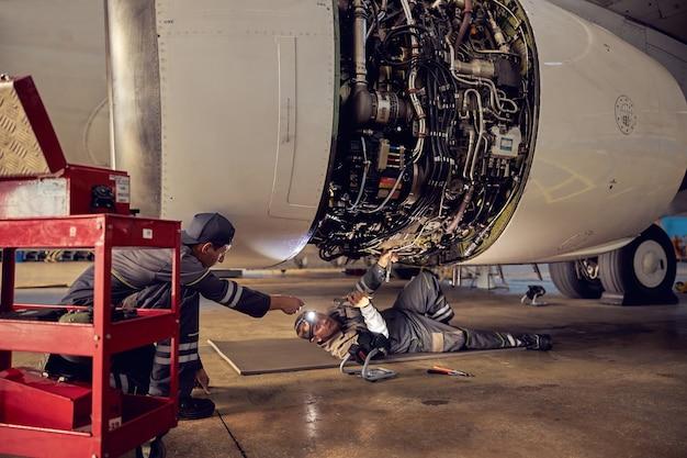 Ritratto di ingegnere aeronautico nell'hangar che ripara e mantiene il motore a reazione dell'aeroplano