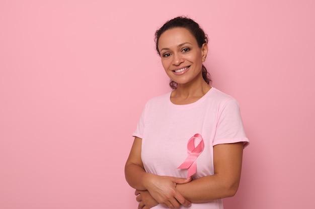 Ritratto di una donna di razza mista altruista e sorridente in una maglietta rosa con un nastro di raso rosa, simbolo della giornata internazionale del cancro al seno. programma educativo per la lotta contro il cancro. 1 ottobre