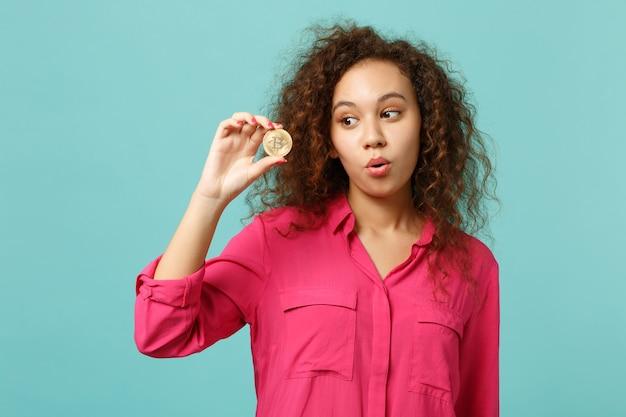 Ritratto di una ragazza africana stupita in abiti casual che tiene bitcoin, valuta futura isolata su sfondo blu turchese in studio. concetto di stile di vita di emozioni sincere della gente. mock up copia spazio.
