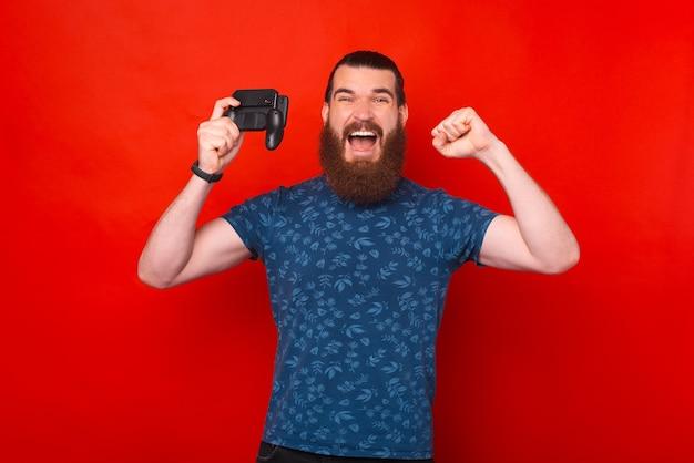 Ritratto di un uomo hipster barbuto stupito che celebra e gioca allo smartphone con joystick