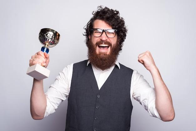 Ritratto dell'uomo barbuto stupito hipster in vestito che tiene tazza e che celebra.