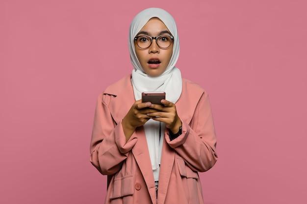 Ritratto di bella donna asiatica stupita che tiene un telefono cellulare