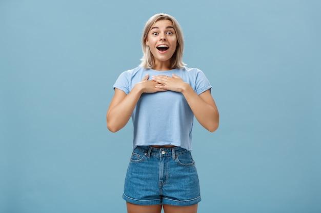Ritratto di studentessa bionda attraente stupita e incantata con pelle abbronzata in pantaloncini di jeans e maglietta estiva che tiene i palmi delle mani sul seno ansimante e sorridente con gioia essendo grato e compiaciuto