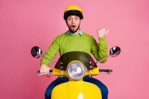 Il ritratto del ragazzo allegro stupito che guida il ciclomotore indica il dito