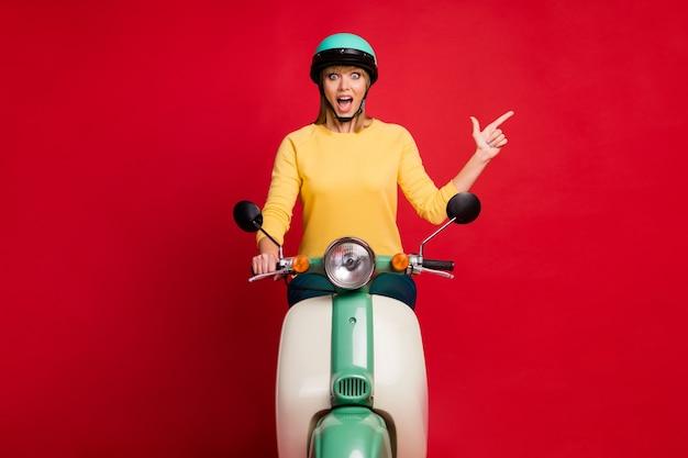Ritratto di ragazza stupita in sella a ciclomotore che mostra lo spazio della copia sulla parete rossa
