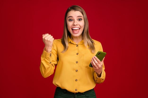 Ritratto di una ragazza stupita che utilizza la connessione rapida dell'app di vendita cellulare isolata su uno sfondo di colore rosso
