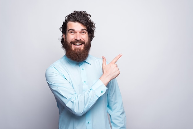 Ritratto di uomo stupito con la barba che indossa la camicia blu e che punta lontano.