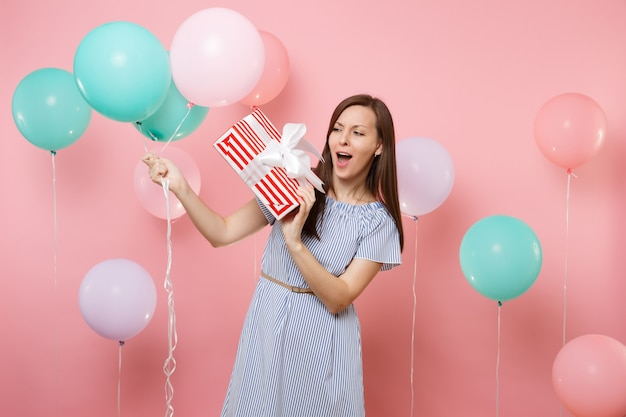 Ritratto di una bella giovane donna stupita che indossa un abito blu che guarda una scatola rossa con un regalo che tiene in mano palloncini colorati su sfondo rosa. festa di compleanno, concetto di emozioni sincere della gente.