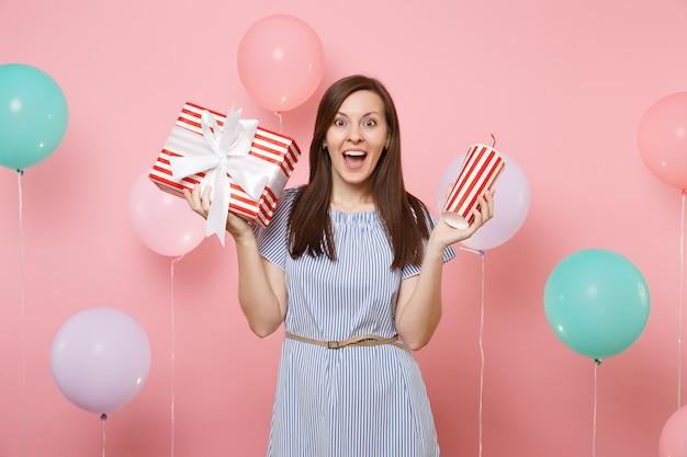 Ritratto di donna stupita in abito blu con scatola rossa con regalo regalo e tazza di plastica di soda o cola su sfondo rosa con mongolfiere colorate. festa di compleanno, persone sincere emozioni.