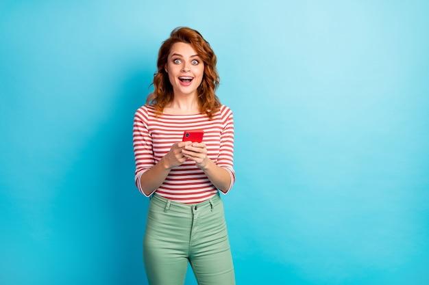 Ritratto di donna stupita usa il cellulare ottiene notifica di social network impressionato urlo wow omg indossare maglione elegante isolato su colore blu