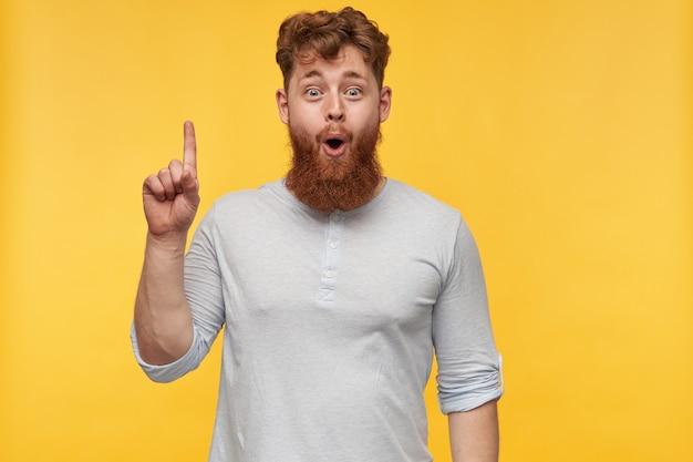 Ritratto di stupito giovane ragazzo barbuto con i capelli rossi, sorride ampiamente con felice espressione facciale, punta con un dito verso l'alto.