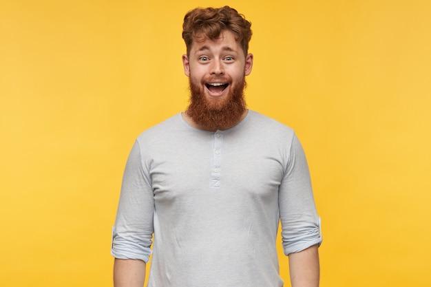 Ritratto di stupito giovane ragazzo barbuto con i capelli rossi, sorride ampiamente con felice espressione facciale. ritratto di ragazzo gioiosa rossa su giallo