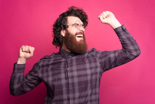 Ritratto di giovane uomo barbuto stupito che grida e celebra la vittoria