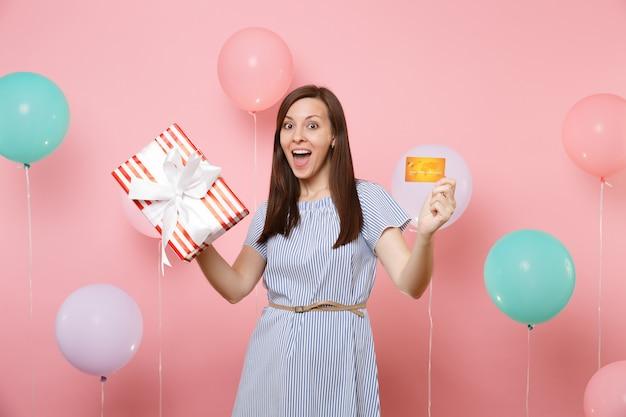 Ritratto di giovane donna stupita in abito blu con carta di credito e scatola rossa con regalo presente su sfondo rosa pastello con mongolfiere colorate. festa di compleanno, persone sincere emozioni.