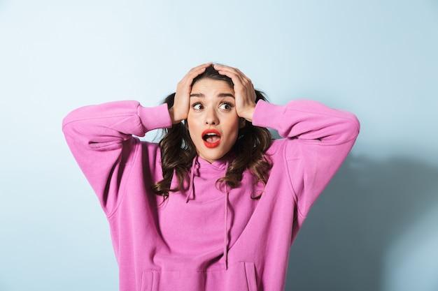 Ritratto di giovane donna stupita con due code di cavallo chiedendosi e afferrando la sua testa sopra l'azzurro in studio