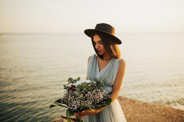 Ritratto di incredibile sposa in tenero abito blu e cappello nero in piedi sulla spiaggia al tramonto, guardando il suo bouquet da sposa.