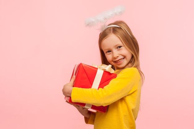 Ritratto di una fantastica bambina allo zenzero con lentiggini e aureola angelica che abbraccia una scatola avvolta, godendosi il regalo di compleanno, soddisfatta del regalo tanto atteso. studio al coperto isolato su sfondo rosa