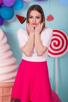 Ritratto di un'incredibile donna golosa in abito rosa che tiene caramelle e posa su uno sfondo decorato con un enorme gelato. anguria lecca-lecca