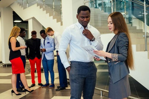 Ritratto di ambizioso team di affari di diverse etnie multinazionali in abito elegante che comunicano insieme nella hall dell'ufficio moderno.