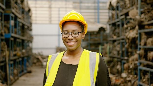 Il ritratto della donna africana americana di ingegneria sta lavorando nella fabbrica delle parti del motore dell'impianto industriale pesante.