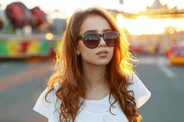 Ritratto di hipster americano carino giovane rossa con labbra sexy in occhiali da sole alla moda in una maglietta bianca alla moda in un parco di divertimenti