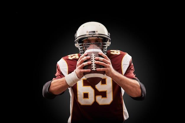 Ritratto del giocatore di football americano che tiene una palla con entrambe le mani