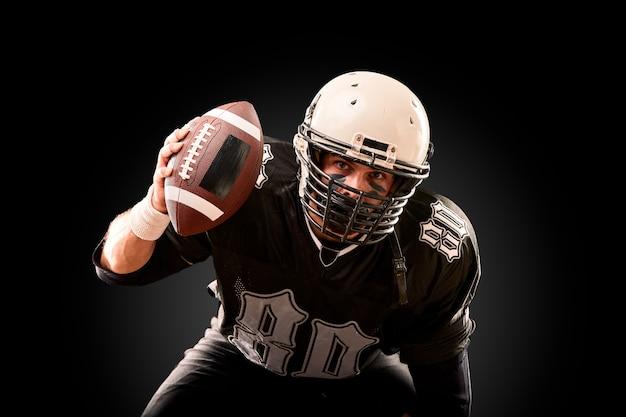 Ritratto del giocatore di football americano con il casco da vicino, su sfondo nero