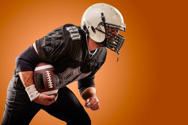 Ritratto del giocatore di football americano con il casco si chiuda su sfondo marrone