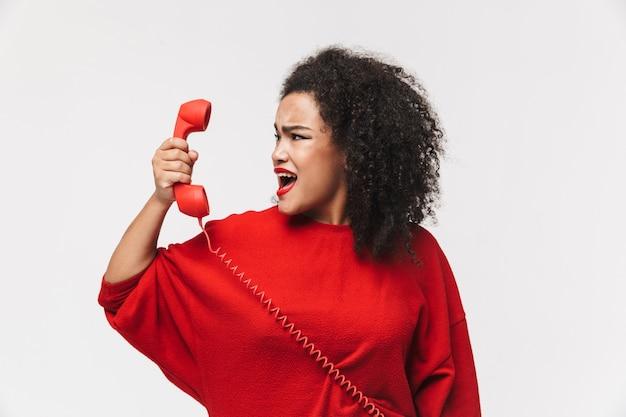 Ritratto di una donna africana arrabbiata in piedi isolata su sfondo bianco, parlando su un telefono fisso