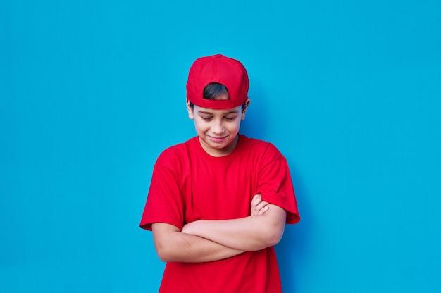 Un ritratto di ragazzo arrabbiato in berretto rosso e t-shirt con gli occhi chiusi e guardando in basso