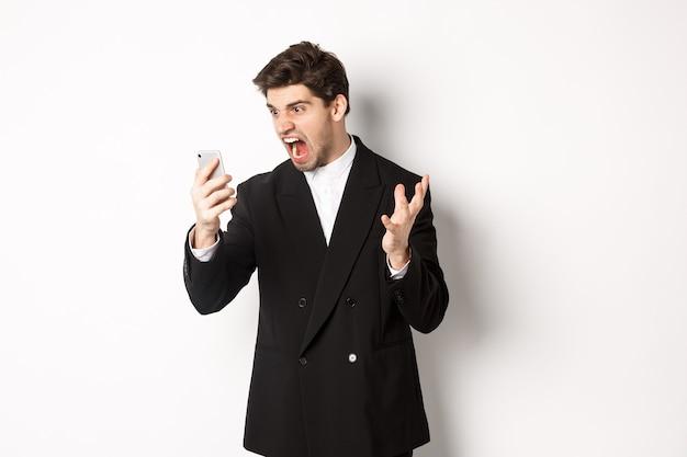 Ritratto di uomo d'affari arrabbiato in abito nero che urla al telefono cellulare, avendo una discussione in videochiamata, in piedi matto su sfondo bianco.