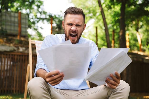 Ritratto di uomo adulto furioso arrabbiato seduto in poltrona, durante il resto nel parco verde e in possesso di documenti cartacei