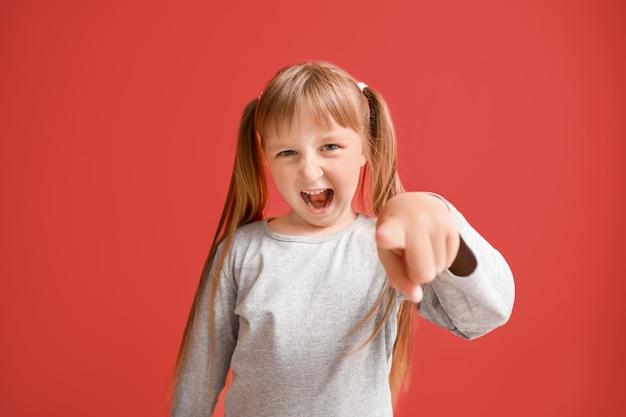 Ritratto della bambina arrabbiata sul colore